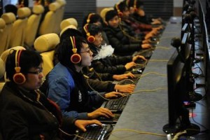A man smokes while using a computer at an Internet cafe in Taiyuan