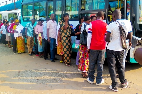 Rwandans queue up next to a bus