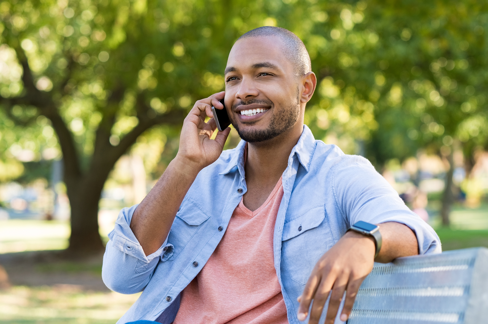 Handsome african man talking on phone at park. Young black man talking on cellphone while sitting on bench outdoor. African american smiling guy in a happy conversation at mobile phone.