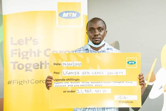 A Red cross Official Displays the Cheque containing the donation by MTN customers to fight Covid19