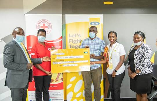 RedCross' Josephine Okwera (2L) and her team, Received the cheque from MTN's Rhona Arinaitwe (2R)
